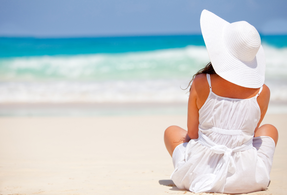 Peaceful woman at the beach contemplating the ocean and relaxing